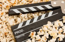 Movie clapperboard laying on top of popcorn - movie themes